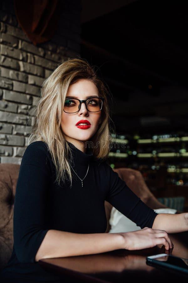Młody uśmiechnięty biznesowej kobiety obsiadanie w kawiarni przy stołem, opartą ręką na stole i mienia smartphone, zdjęcia royalty free