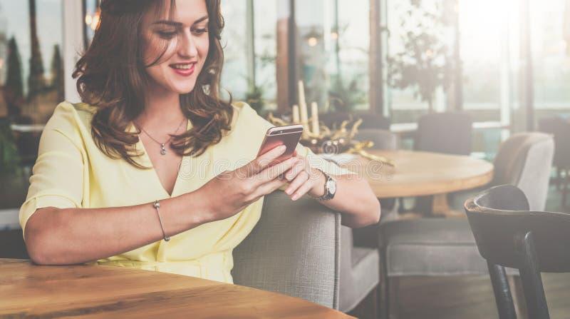 Młody uśmiechnięty bizneswomanu obsiadanie w kawiarni przy stołem, używać smartphone i patrzejący jego ekran młody pracy kobiet fotografia stock