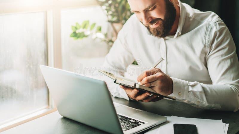 Młody uśmiechnięty brodaty biznesmen w białym koszulowym obsiadaniu przy biurkiem przed laptopem, robi notatkom w notatniku zdjęcie royalty free
