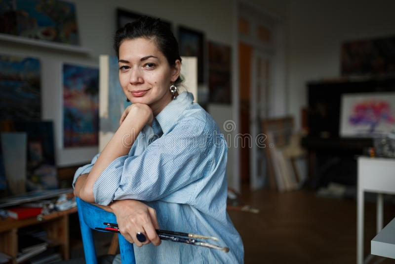 Młody uśmiechnięty brunetki kobiety artysta w jej studiu fotografia stock