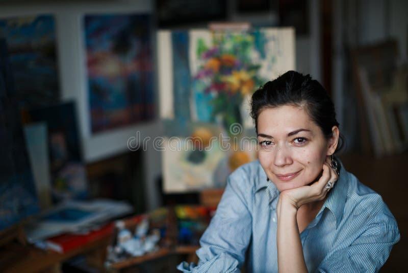 Młody uśmiechnięty brunetki kobiety artysta w jej studiu obrazy stock