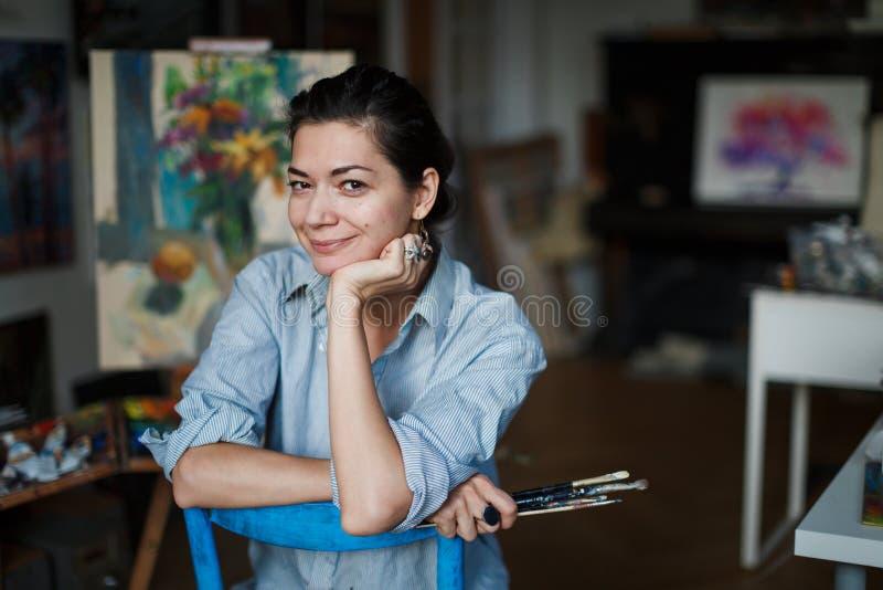 Młody uśmiechnięty brunetki kobiety artysta w jej studiu zdjęcie royalty free
