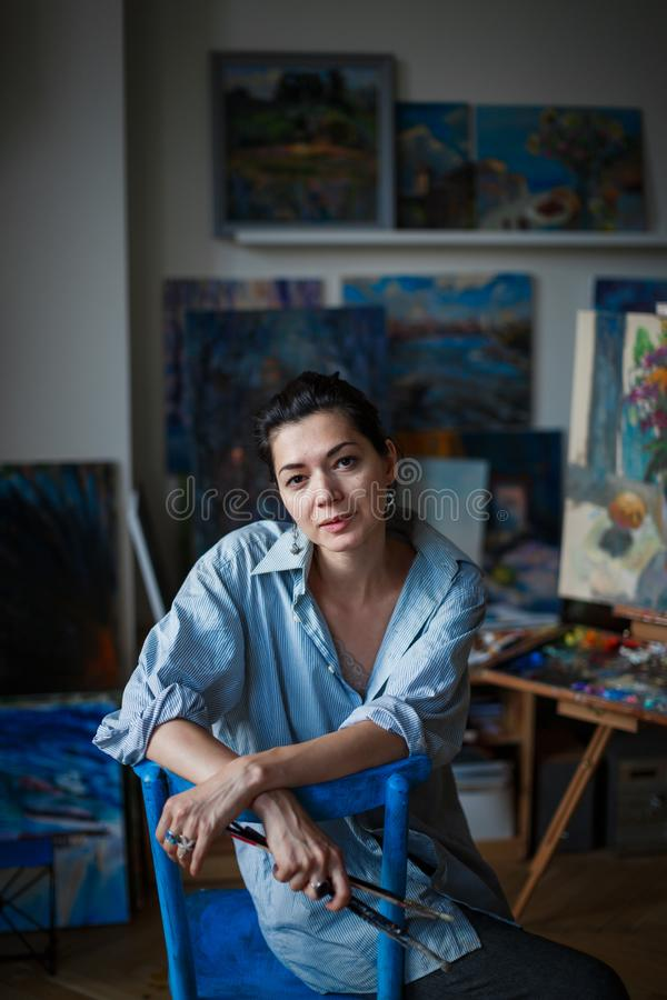 Młody uśmiechnięty brunetki kobiety artysta w jej studiu obraz royalty free