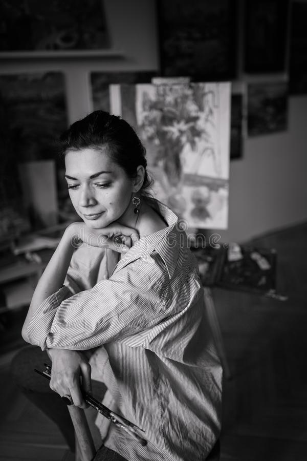 Młody uśmiechnięty brunetki kobiety artysta w jej studiu fotografia royalty free