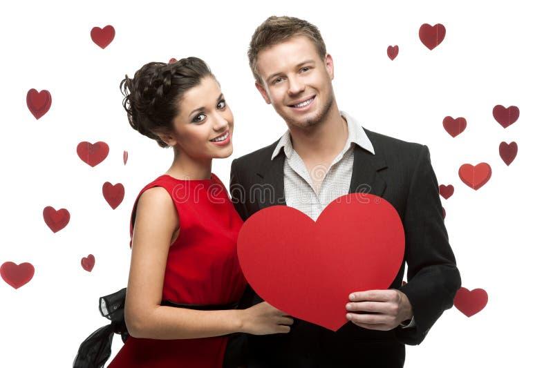 Młody uśmiechnięty caucasian pary mienia czerwieni serce obrazy stock