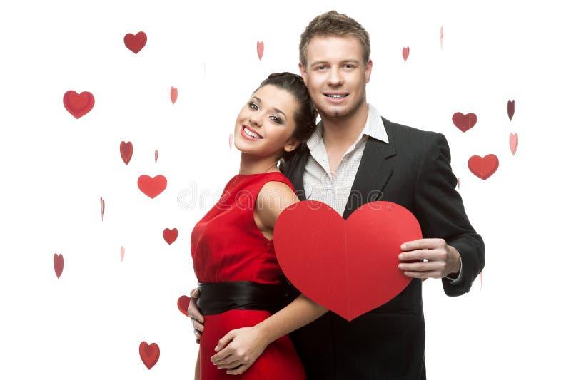 Młody uśmiechnięty caucasian pary mienia czerwieni serce zdjęcie royalty free