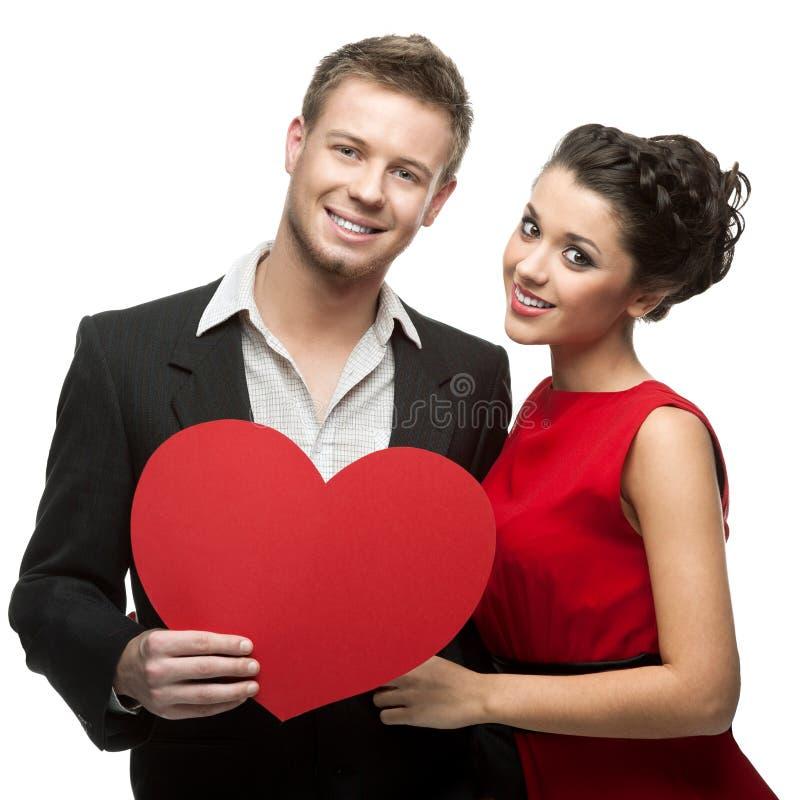 Młody uśmiechnięty caucasian pary mienia czerwieni serce fotografia stock