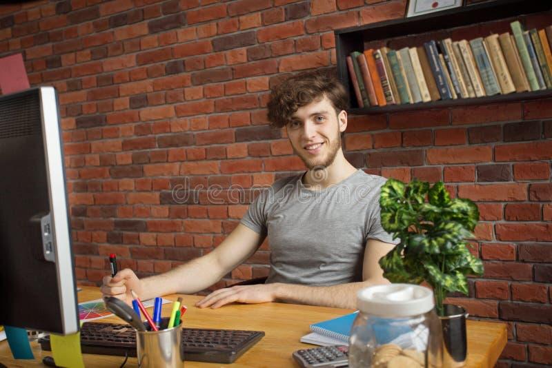 M?ody u?miechni?ty cyfrowy artysta pracuje przy jego miejsce pracy patrzeje ?yczliwy w loft stylu biurze obrazy stock
