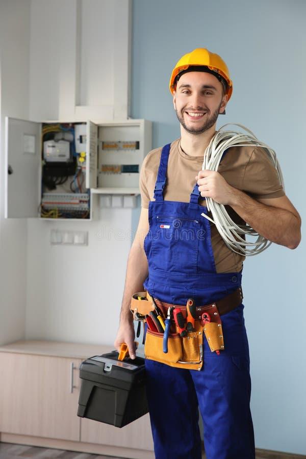 Młody uśmiechnięty elektryk z wiązką druty fotografia royalty free