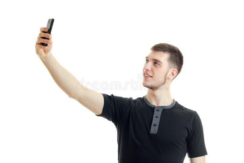 Młody uśmiechnięty facet w czarnej koszula podnosił jego rękę up i robi fotografii na telefonie zdjęcia stock