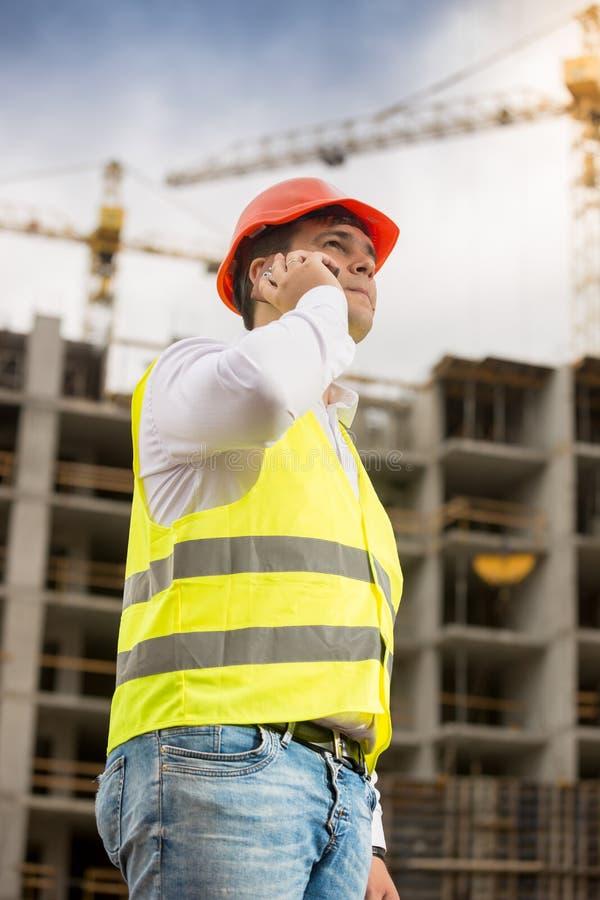 Młody uśmiechnięty inżynier opowiada telefonem przy budynkiem pod constr obrazy stock