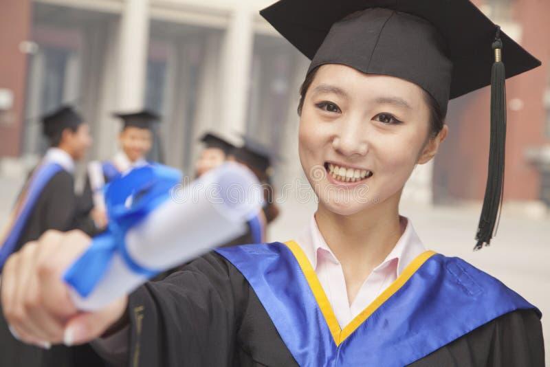 Młody uśmiechnięty kobieta absolwent jest ubranym togę trzyma dyplom skalowania mortarboard i obraz stock