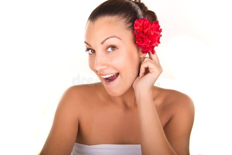 Młody uśmiechnięty kobiety twarzy portret z czerwonymi kwiatami obraz stock