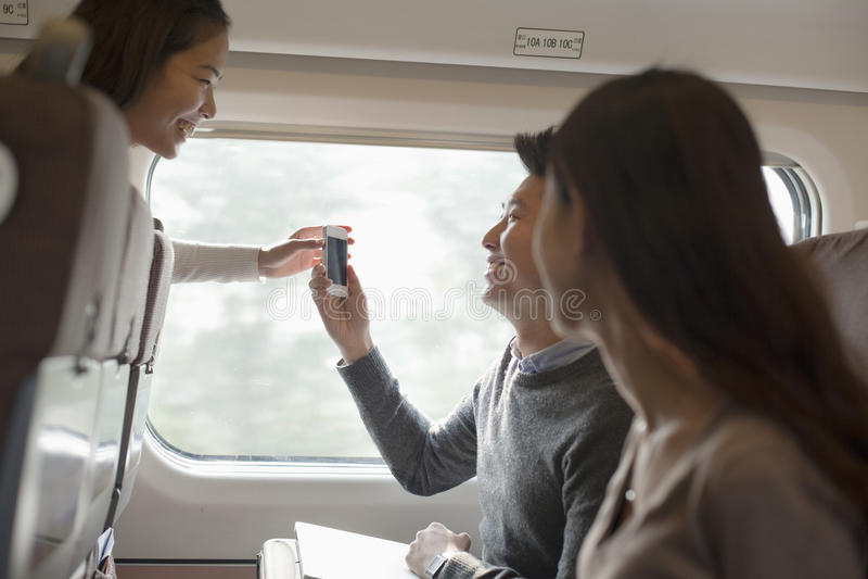 Młody uśmiechnięty mężczyzna i kobiety używa telefon na pociągu, Pekin fotografia stock