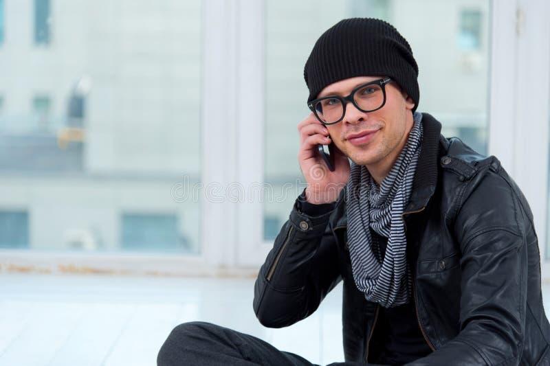 Młody uśmiechnięty mężczyzna opowiada na telefonie obrazy royalty free