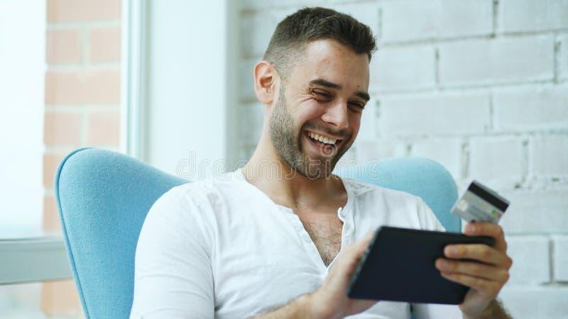 Młody uśmiechnięty mężczyzna robi online zakupy używać cyfrowej pastylki komputerowego obsiadanie przy balkonem w domu zdjęcia stock