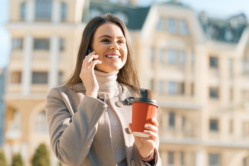 Młody uśmiechnięty piękny kobiety odprowadzenie na ulicie pogodny jesieni miasto opowiada na telefonie komórkowym zdjęcie royalty free
