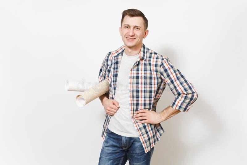 Młody uśmiechnięty przystojny mężczyzna trzyma tapet rolki odizolowywać na białym tle w przypadkowych ubraniach instrumenty fotografia stock
