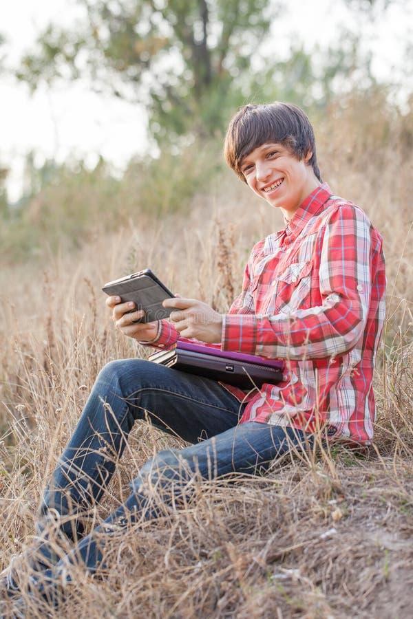 Młody uśmiechnięty studencki działanie w parku fotografia royalty free