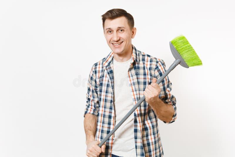 Młody uśmiechnięty szczęśliwy gospodyni mężczyzna w w kratkę koszulowym mieniu i zamiatać z zieloną miotłą odizolowywającą na bie obraz stock