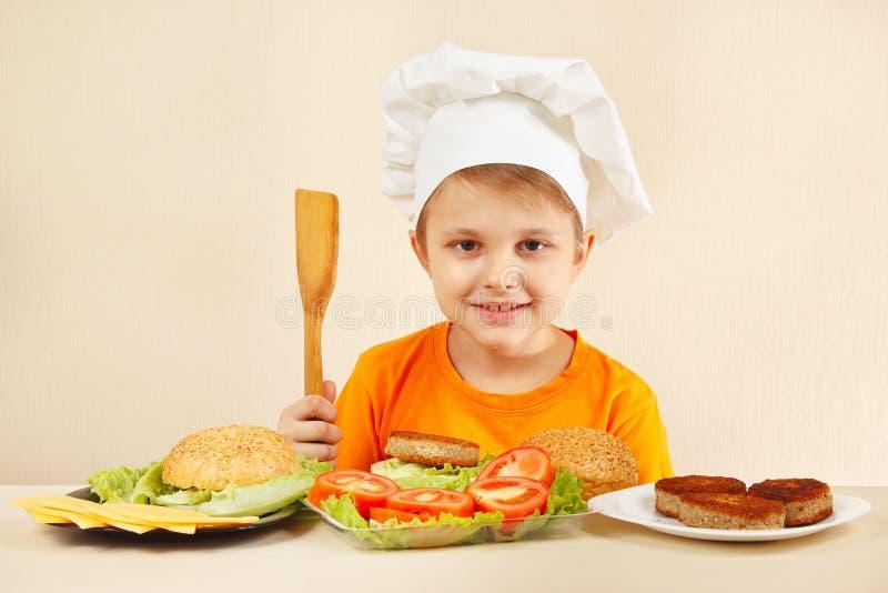 Młody uśmiechnięty szef kuchni przy stołem z składnikami iść gotować hamburger fotografia royalty free