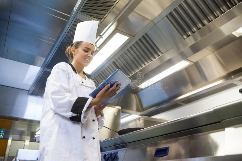 Młody uśmiechnięty szef kuchni używa pastylkę zdjęcia royalty free