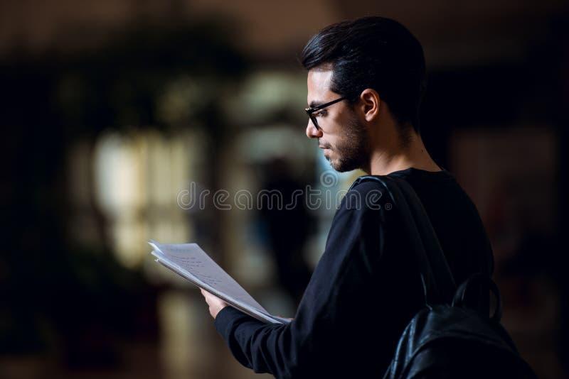 Młody uczeń informatyka konsultuje niektóre papiery iluminujących światłem ekran w korytarzu zdjęcia royalty free
