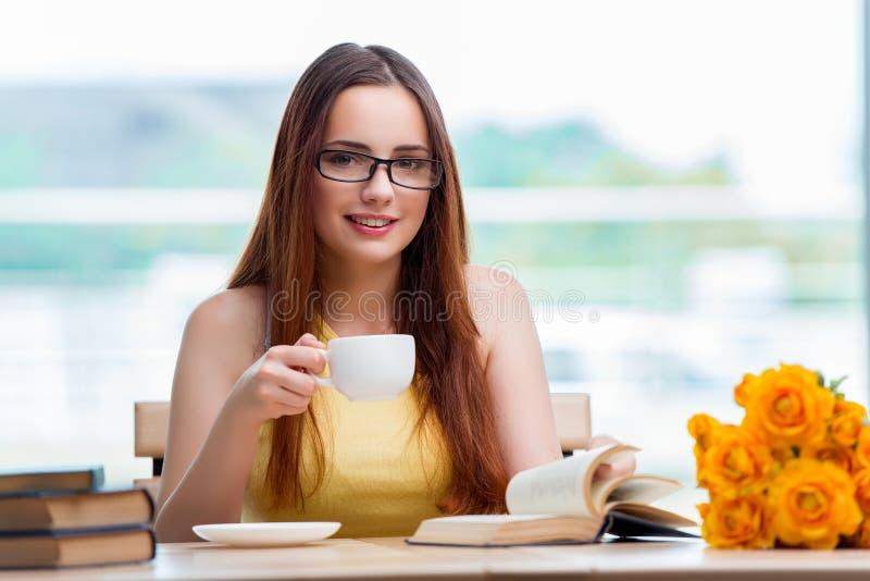 Młody uczeń pije kawę podczas gdy sudying fotografia royalty free