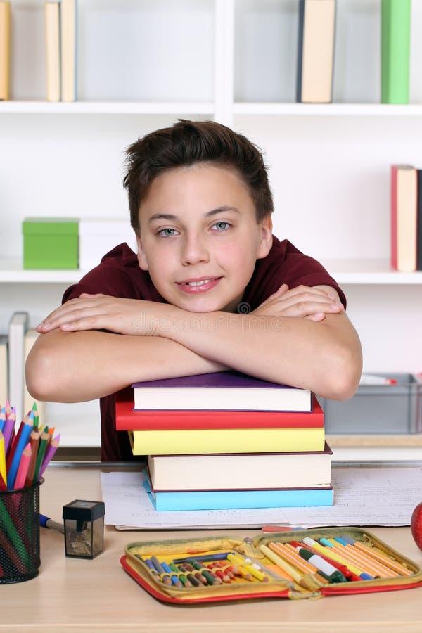 Młody uczeń trzyma jego głowę na stercie książki przy szkołą fotografia royalty free