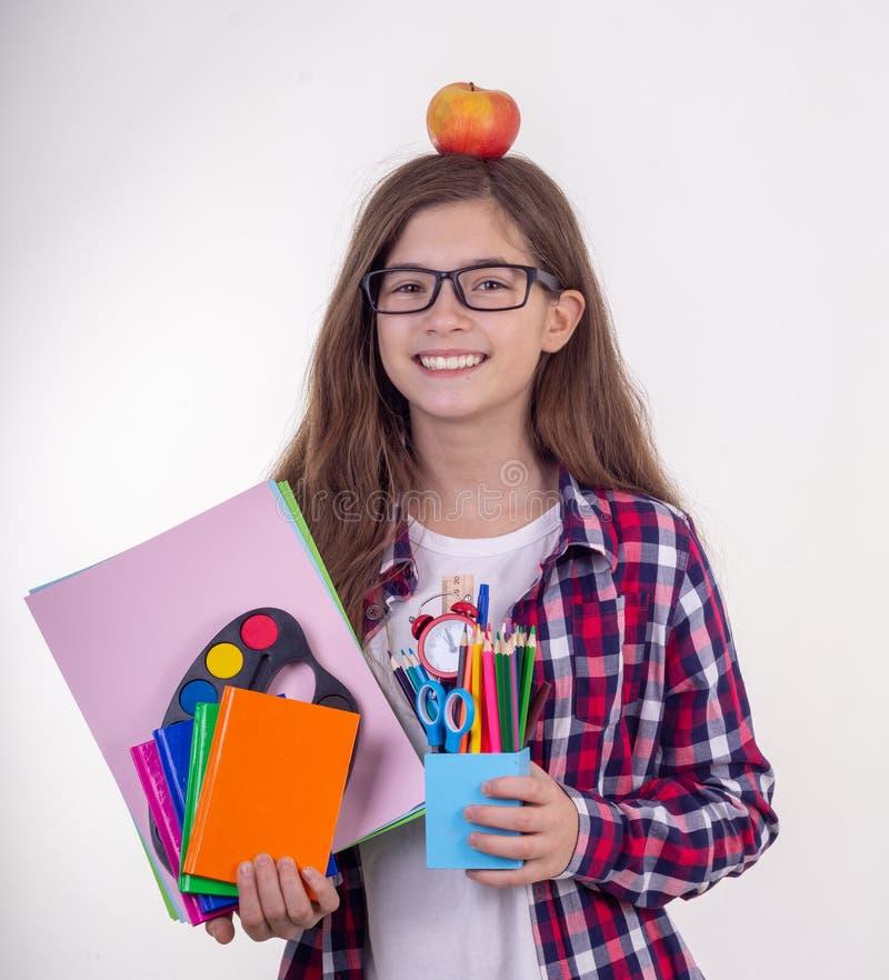 Młody uczeń trzyma szkolne lub biurowe dostawy w eyeglasses: pióra, notatniki, nożyce i jabłko, Popiera szkoła wyższa lub uniwers fotografia royalty free