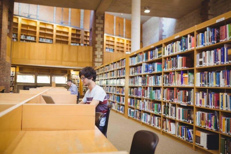 Młody uczeń używa jego laptop w bibliotece obraz royalty free