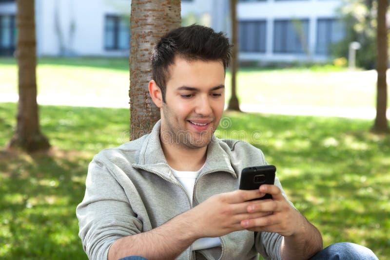 Młody uczeń w parkowej writing wiadomości tekstowej zdjęcie stock