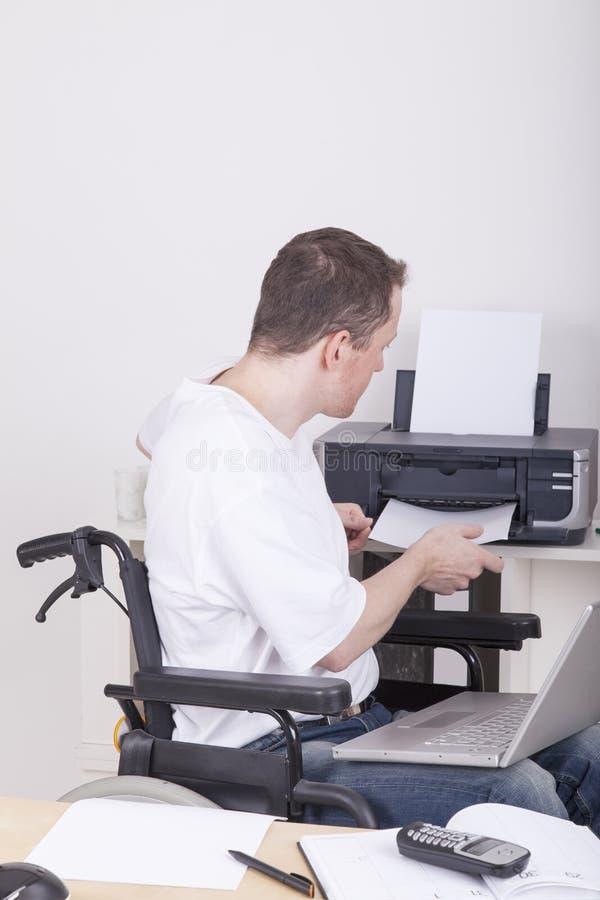 Młody uczeń w wózek inwalidzki biurze w domu obrazy royalty free