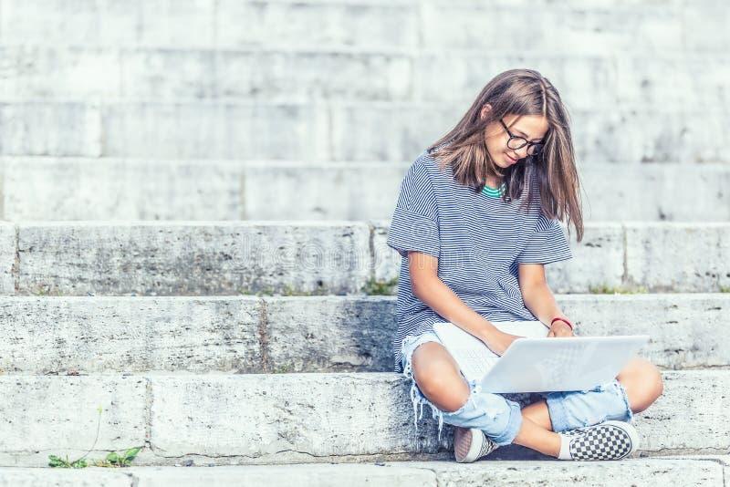 Młody uczennicy obsiadanie na schodkach z internetem lub socjalny siecią laptopu i dopatrywania obrazy royalty free