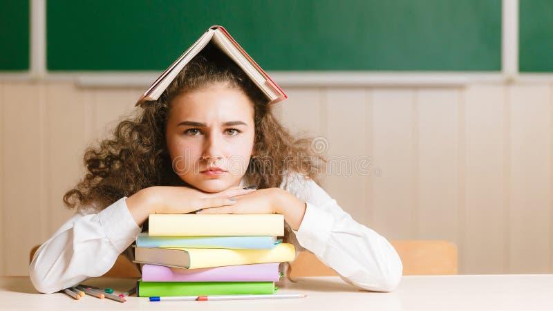 Młody uczennicy obsiadanie przy jej biurkiem na tle mienie i blackboard książka na jej głowie fotografia royalty free