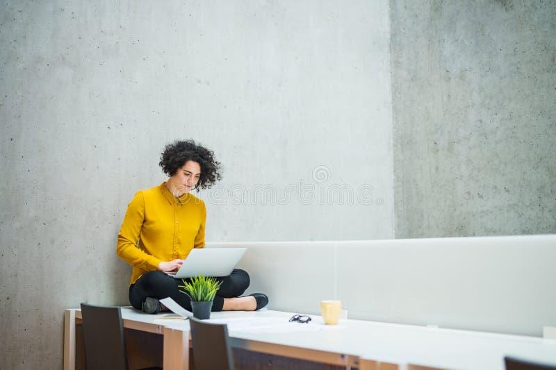 Młody ucznia, bizneswomanu obsiadanie na biurku w pokoju w lub, używać laptop zdjęcia stock