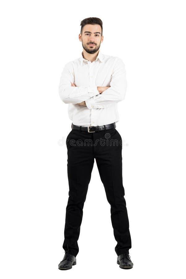 Młody ufny biznesowy mężczyzna patrzeje kamerę z krzyżować rękami fotografia stock