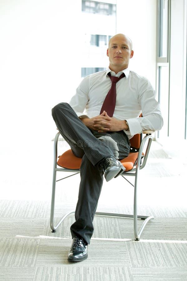 młody ufny caucasian biznesmena obsiadanie na biurowym krześle zdjęcia stock