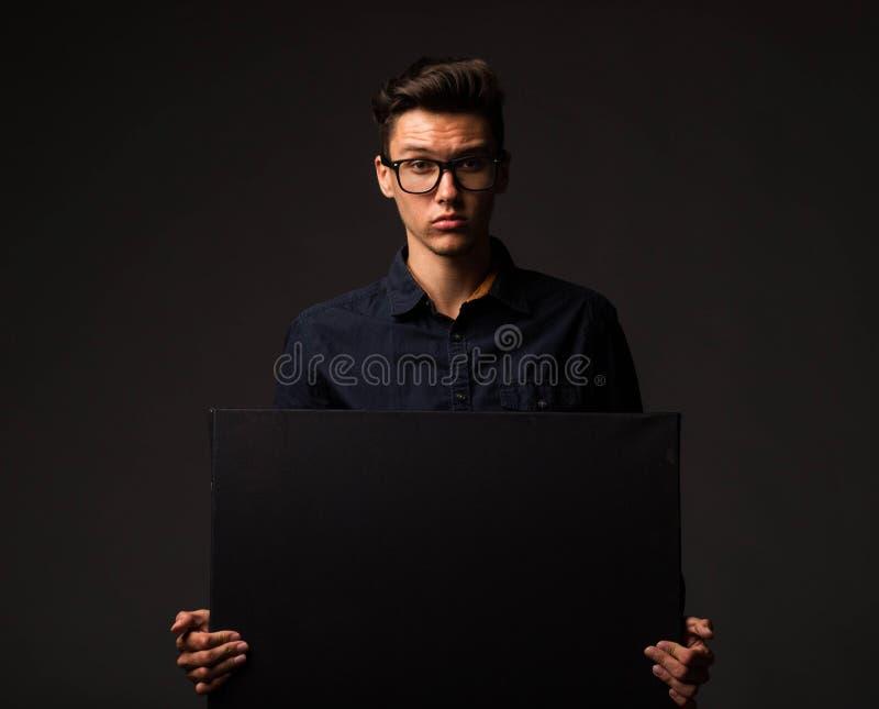 Młody ufny mężczyzna pokazuje prezentację, wskazuje na plakacie obrazy stock