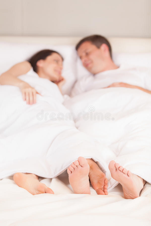 Młody uroczy pary lying on the beach w łóżku obrazy stock