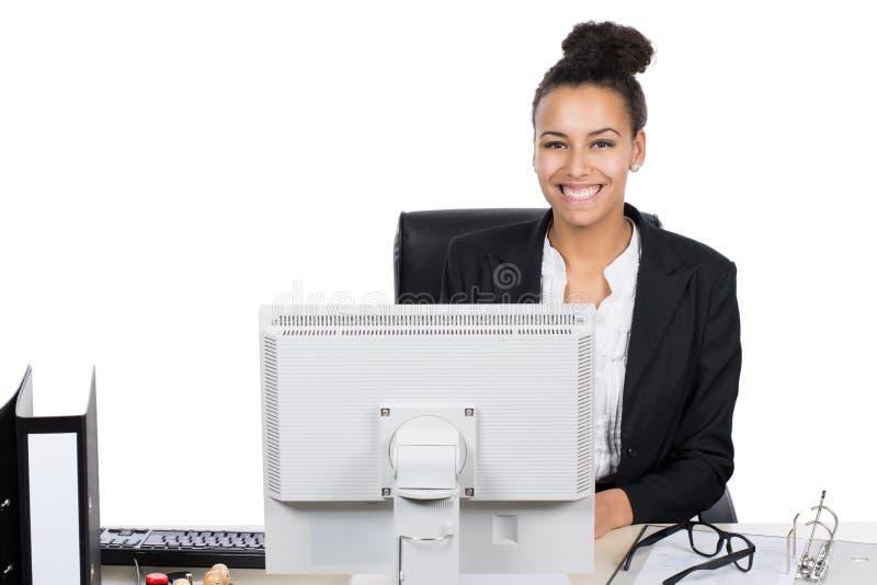 Młody urzędnik siedzi przed komputerem osobistym zdjęcia stock