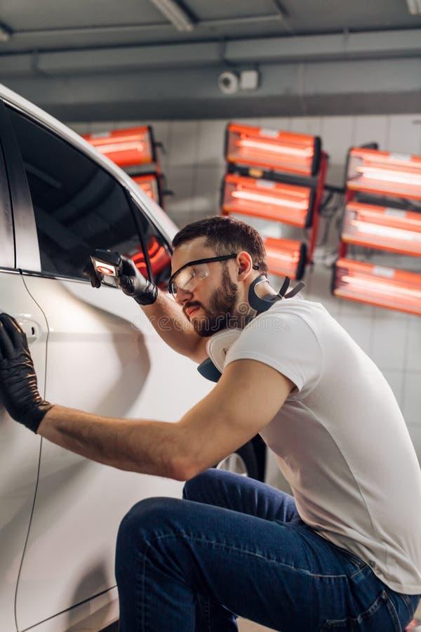Młody utalentowany mechanik sprawdza ilość obraz zdjęcie royalty free