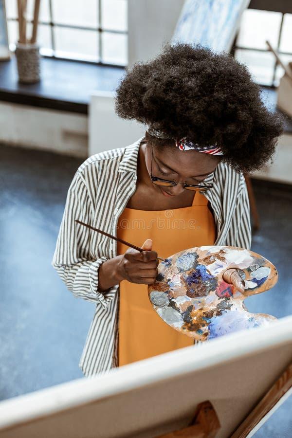 M?ody utalentowany sztuka ucze? miesza kolory dla jej abstrakcjonistycznego kawa?ka zdjęcie royalty free