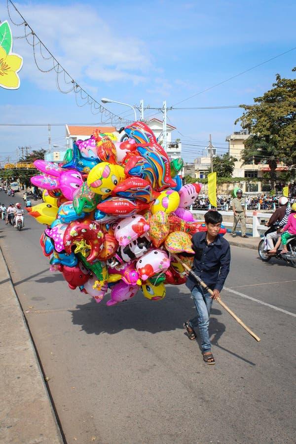 Młody vietnmese mężczyzna sprzedaje kolorowych balony na ulicie podczas n obraz stock