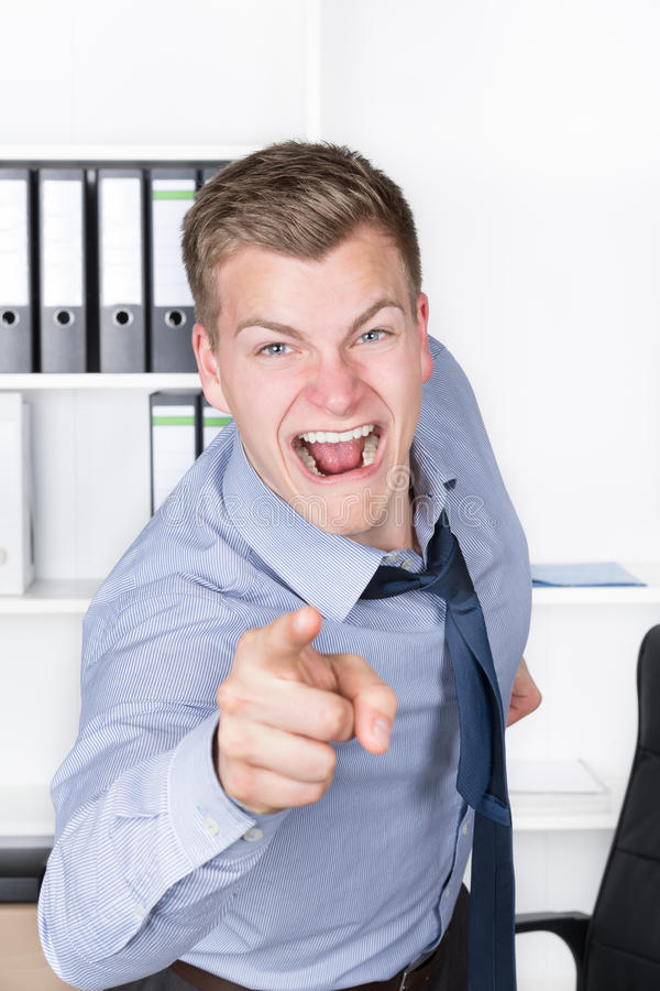 Młody wściekły mężczyzna wskazuje z jego palcem w biurze zdjęcia royalty free