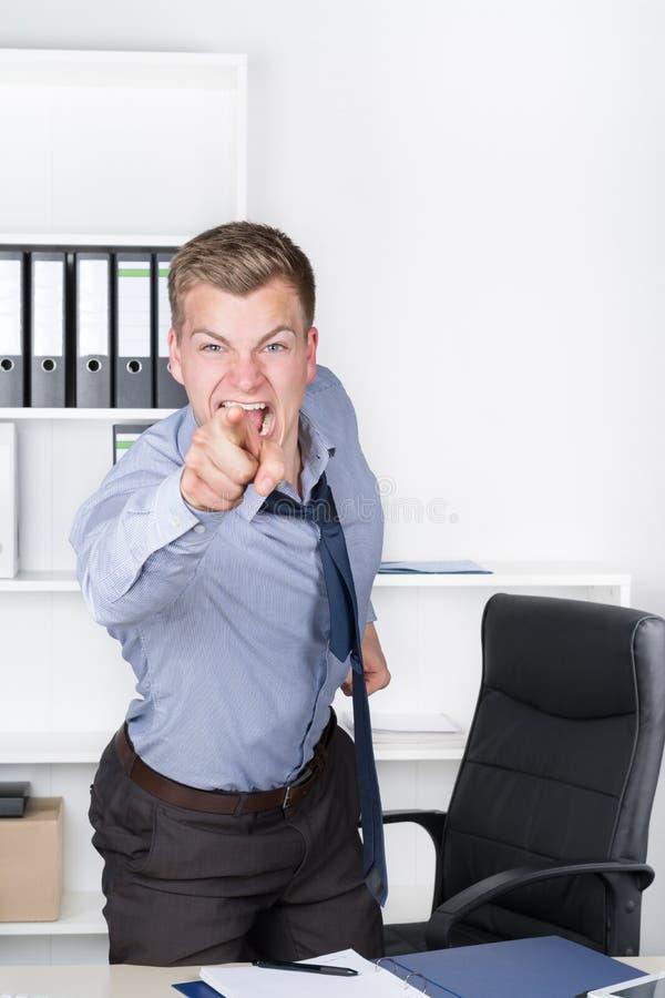 Młody wściekły mężczyzna wskazuje z jego palcem w biurze obrazy royalty free