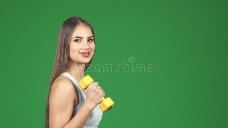 Młody wspaniały szczęśliwy sportsmenki ono uśmiecha się pracujący z dumbbells out zdjęcie stock