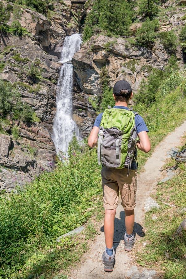 Młody wycieczkowicz z plecakiem na halnej ścieżce, Lillaz siklawy blisko Cogne, Granu Paradiso park narodowy, Aosta dolina Alps, obraz royalty free
