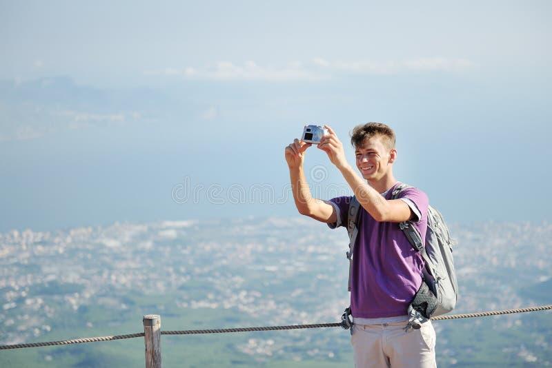 Młody wycieczkowicz z plecakiem ono robi fotografii na wierzchołku halny Vesuvius, Włochy fotografia stock