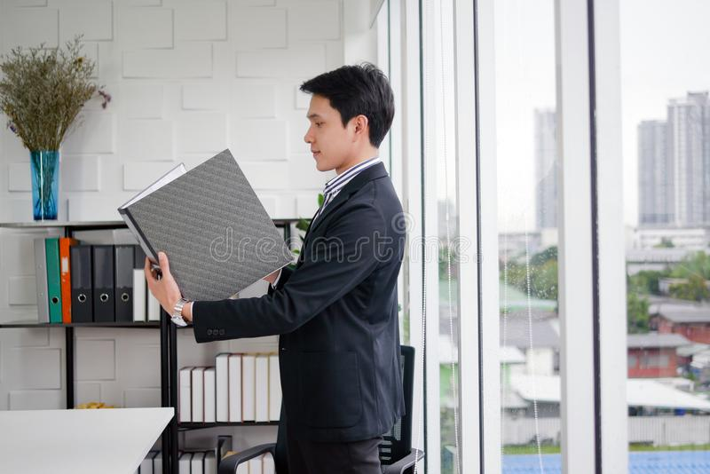 Młody wykonawczy Azjatycki mężczyzna jest stojący czarnej kartoteki biznesowego raport w nowożytnym biurowym pokoju i trzymający zdjęcia stock